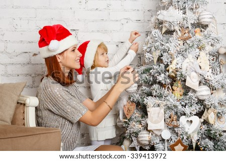 The pretty girl with mum are decorating a Christmas tree in the house. Happy family.