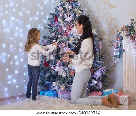 The pretty girl with mum are decorating a Christmas tree in the house. Happy family. Merry Christmas and New Year.