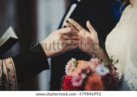 the priest gives the bride   a wedding ring