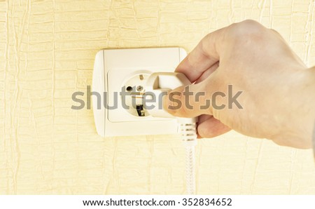 The process of connecting the white plug into the socket on the background of yellow wall