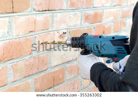 The process of drilling using electric drills on a background of a brick wall