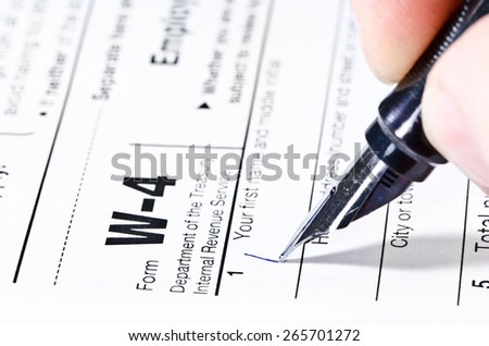 The process of filling out the W-4 form, shallow depth of field - stock photo