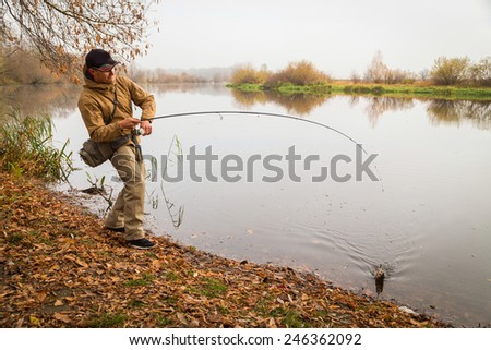 The process of fishing, catching fish. Professional fisherman is fishing on the bank of the river. Fish on the hook fisherman. The concept of outdoor activities - fishing.
