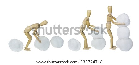 The process of Making a snowman by piling balls of snow together - path included - stock photo