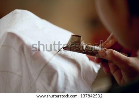 The process of making batik. Application of wax on the fabric. Indonesia. - stock photo