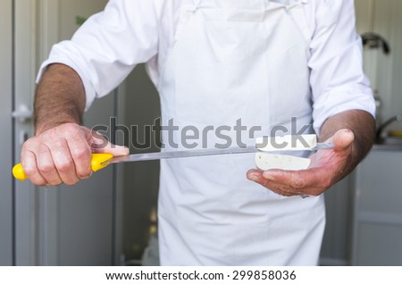 The process of producing tasty traditional white Bulgarian feta cheese at its final stage before packeting. Cutting with a knife. - stock photo