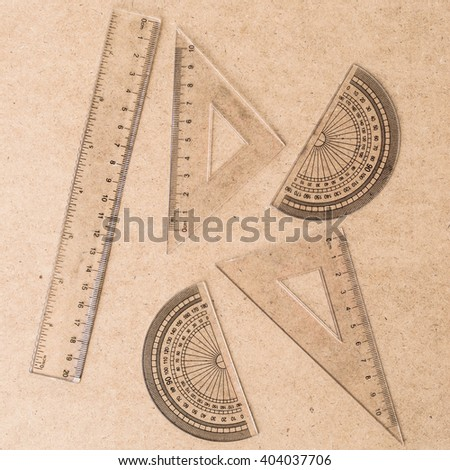 The protractor and ruler on wooden background; Flat lay - stock photo