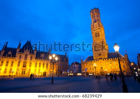 The provincial courthouse and belfry with clock tower are illuminated at dusk blue hour in grote markt, the old city center of Brugge, Belgium - stock photo