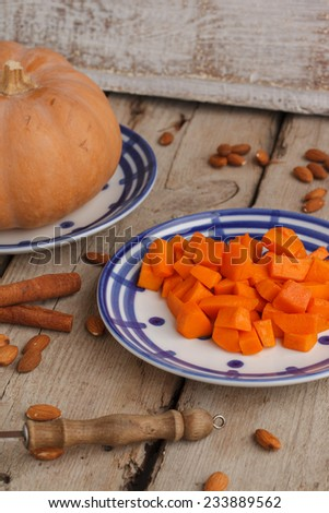 The pumpkin pieces on a wooden table. - stock photo