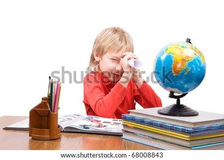 The pupil looks at the globe, through a leaf braided in the form of a telescope - stock photo
