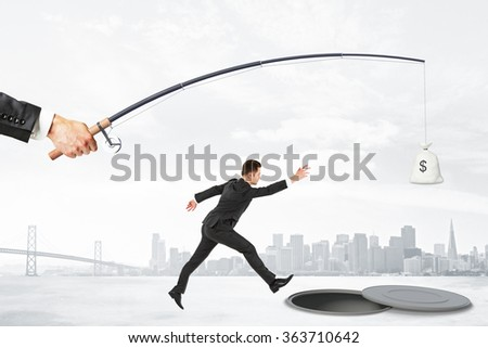 The pursuit of money with businesman jumping into the abyss and rod with a bag of money - stock photo