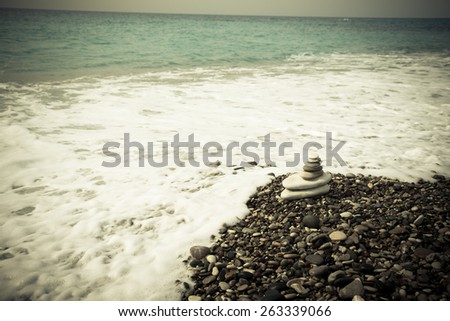 The pyramid of pebbles on the beach. - stock photo