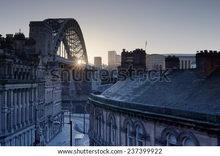 The Quayside at Newcastle upon Tyne and Gateshead photographed as the sun rises behind the Tyne bridge during the morning. - stock photo