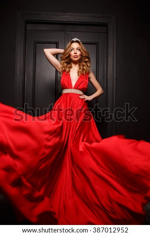 The queen of the ball with tiara on her head and gorgeous body is very sexy and charming in the elegant red evening fluttering dress with deep neckline