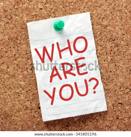 The question Who Are You in red text on a sheet of lined paper pinned to a cork notice board - stock photo