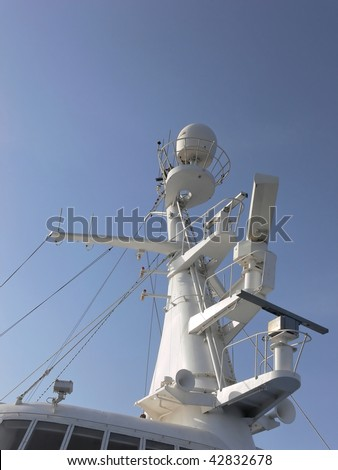 The radar-mast on an cruse ship all in white with blue sky.