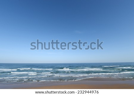 The raging sea splashes against the sand beach shore near Agadir in Morocco. - stock photo