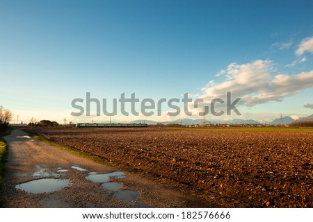 the railway go through the fields in the plan of Friuli Venezia-Giulia - stock photo