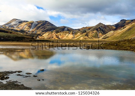 The rainbow rock of Landmannalaugar is reflected in a still lake under a cloudy sky, Iceland. - stock photo