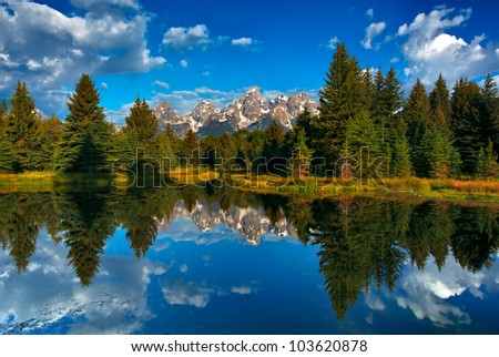The range of tetons are reflected in the water