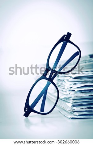 the reading eyeglasses with stacking of newspaper background ,  business information concept - stock photo