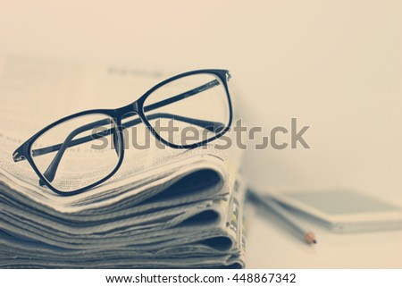 the reading eyeglasses with stacking of newspaper background, business information concept, vintage and retro style