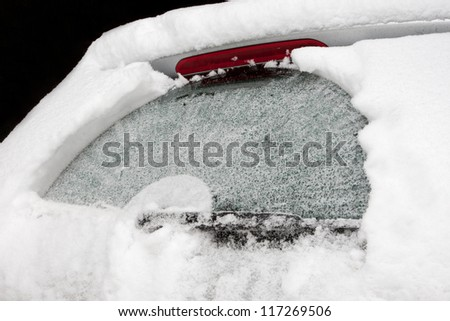 The rear screen of a car covered with ice and snow - stock photo