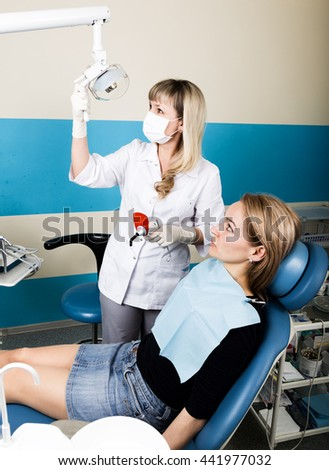 The reception was at the female dentist. Doctor examines the oral cavity on tooth decay. Caries protection. doctor puts the patient an anesthetic injection. - stock photo