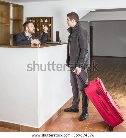 The receptionist and a client disucuss at the hostel reception desk.