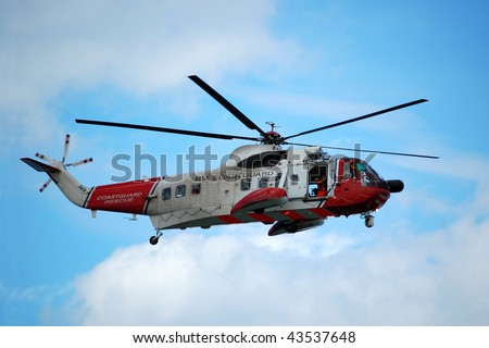 The red and white coastguard helicopter in flight, against a blue summer sky. - stock photo