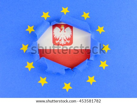 The red and white flag of Poland is shown behind the torn open center of the blue flag of the European Union with gold stars. The EU flag is highly textured construction paper.  - stock photo