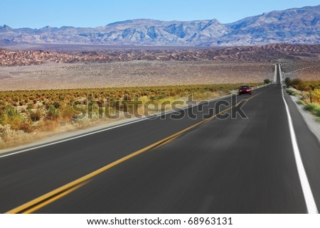 The red car was going at high speed, crossing Death Valley in the USA. The low dry bushes and mountains - stock photo