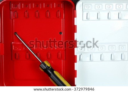 The red color small key box cabinet with screwdriver represent the office supply equipment and hardware concept related idea.