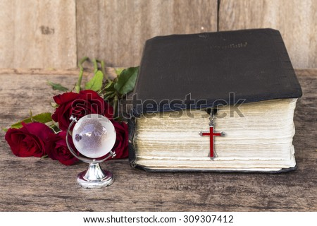 The red cross  hanging with the old  bible with red roses  and  the world globe model on wooden background, world mission concept.  - stock photo