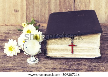 The red cross  hanging with the old  bible with white flowers  and the world globe model on wooden background, world mission concept.  - stock photo