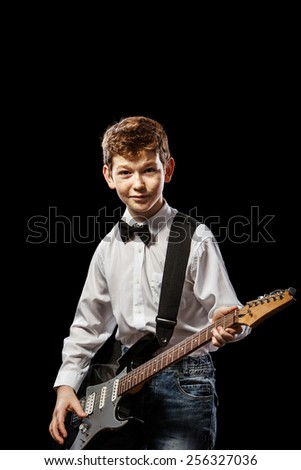 The red-haired boy in a white shirt with an electric guitar on a black background - stock photo