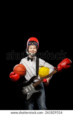 The red-haired boy with a variety of implements on itself on a black background - stock photo