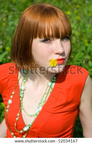 The red-haired girl with a dandelion in a mouth