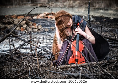 The red-haired girl with a violin sitting on the ashes - stock photo
