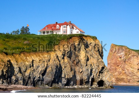 The Red House on top of the cliff on the edge of the water.Percé (City) Quebec, Canada - stock photo