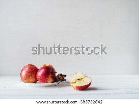 The red juicy apples and cinnamon sticks on a plate. Half of apple on a wooden table. - stock photo