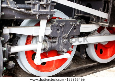 The red old locomotive wheels close up.