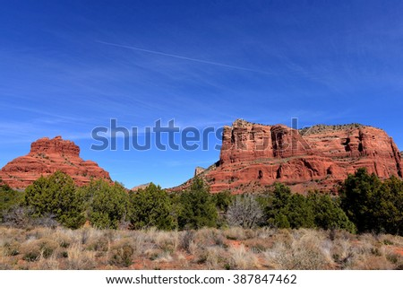 The red rock formations of Sedona Arizona, featuring Bell Rock on the left and jet with vapor trail in the sky. - stock photo