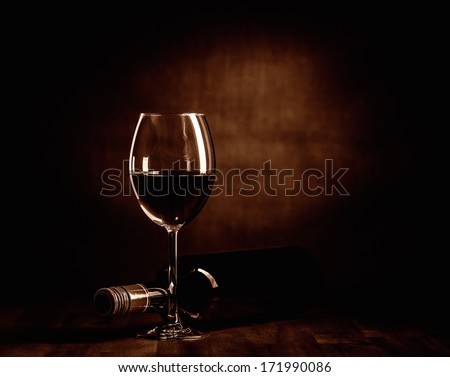 The red wine bottle and full glass on the table, dark brown theme and canvas background