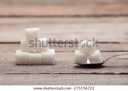 The refined sugar in cubes in a tea spoon on a wooden table from old boards and the laid-out pyramid from sugar cubes. - stock photo