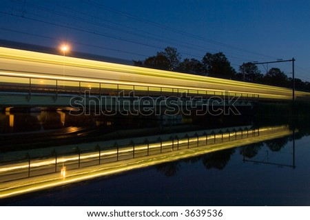 The reflection of an intercity train on a bridge at night - stock photo