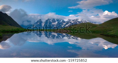 The reflection of the huge mountains in the lake. 30 seconds exposure. - stock photo
