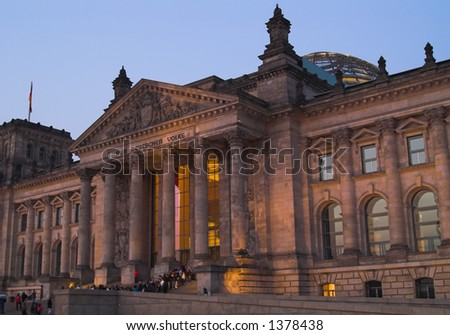 The Reichstag building of Berlin, night view. Reichstag is a residence of German Parliament. There are tourists on the stairs waiting to visit glass dome on the top of reichstag. - stock photo