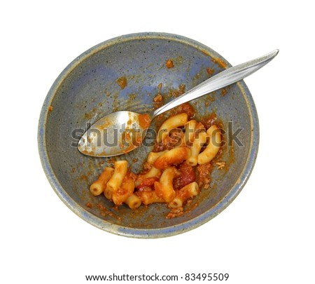 The remains of a macaroni and beef meal in an old bowl with spoon on a white background. - stock photo