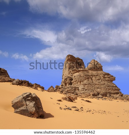 The removed rocks the remains of ancient volcanoes in the middle of the Libyan Desert. Dense sand with edge structure. Southern Libya.